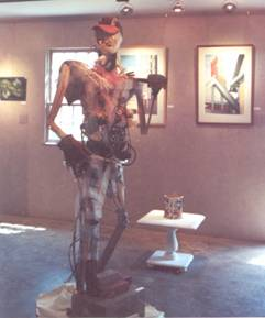 Constructed Worker by Mitch Gordon, composed of found scrap building materials and baseball cap donated by painter Jerome Gonsalves.  In background are works by Bob Kimberly and Peter Hussey.